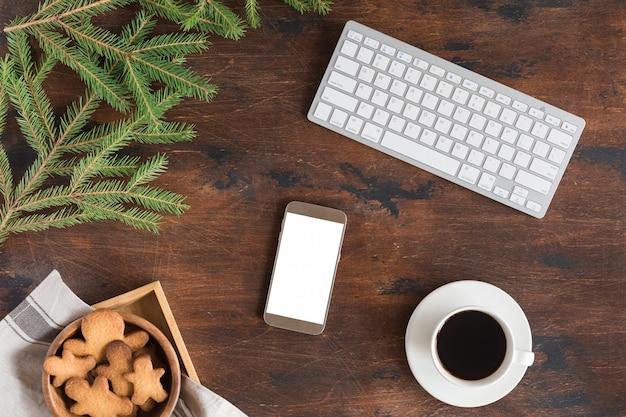 クリスマスのモミの木の枝、携帯電話、ジンジャーブレッドマン、コーヒーカップ、木製のコンピューターまたはラップトップのキーボードのフラットレイアウト