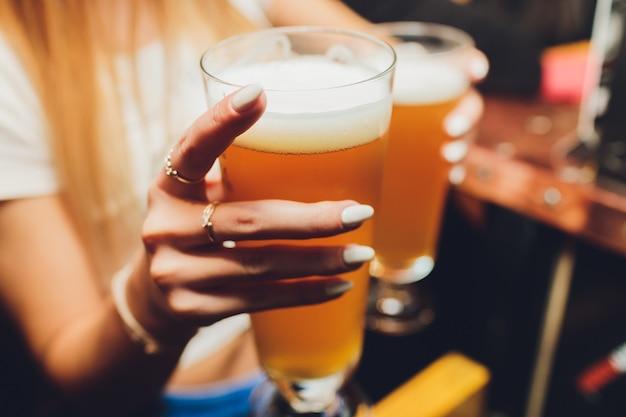 Официант подает бокалы с холодным пивом на подносе