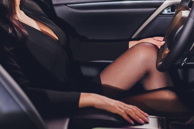 Длинные женские ножки на руле авто.
