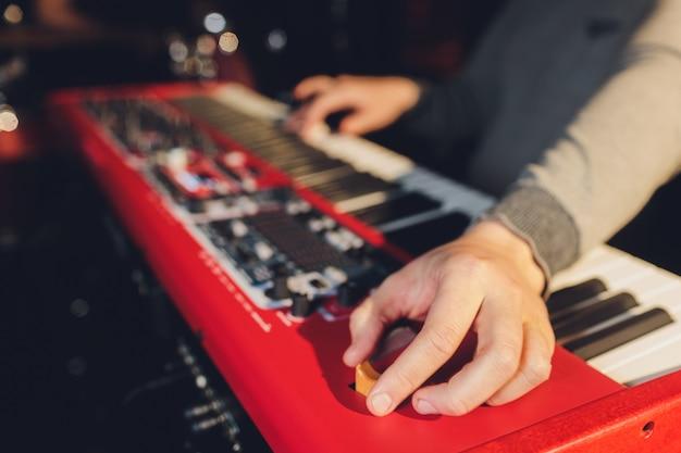 キーボードシンセサイザーのピアノのキーで演奏するミュージシャン。ミュージシャンはコンサートステージで楽器を演奏します。