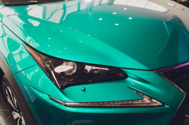 車のターコイズブルーのボディのクローズアップのヘッドライトをクローズアップ。