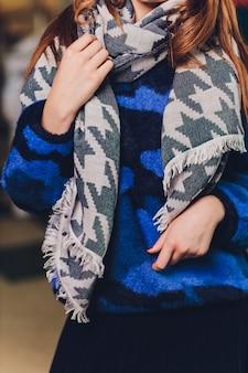 Женщина с шарфом и синим свитером