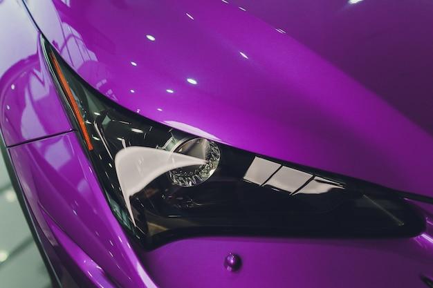 車のクローズアップのヘッドライトバイオレットボディのクローズアップ。