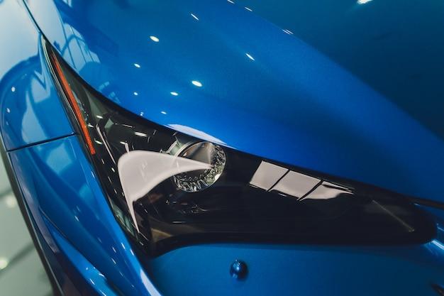 Фары крупного плана конца-вверх тела автомобиля голубого.