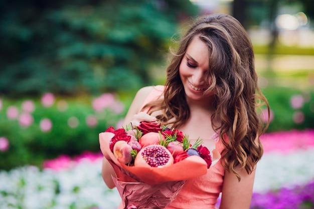 Молодая женщина, держащая букет фруктов и ягод