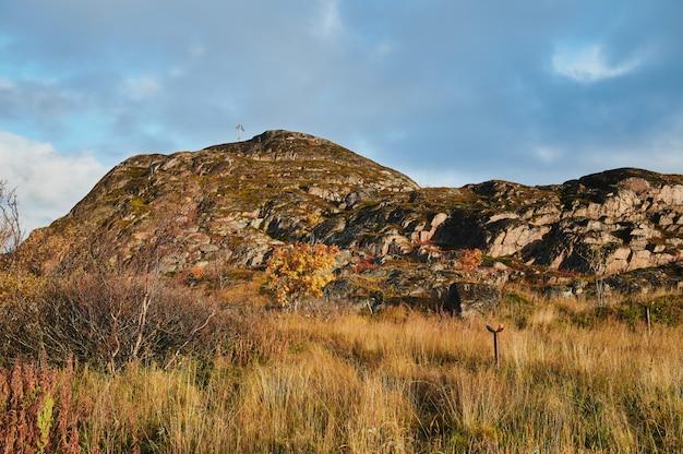 Северная проселочная дорога среди холмов с красочными деревьями и кустарниками тундры осени на пасмурный день.
