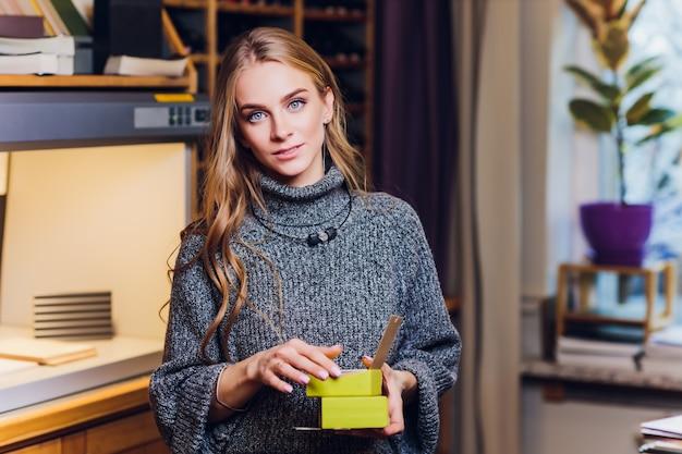 オフィスの机に座って笑顔の女性インテリアデザイナーの肖像画。色比較機器