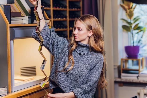Портрет усмехаясь женского дизайнера по интерьеру сидя на столе офиса. оборудование для сравнения цветов