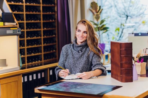 Портрет усмехаясь женского дизайнера по интерьеру сидя на столе офиса.