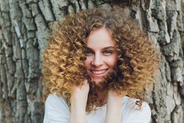 彼女の後ろの木が公園に立っている若い女性のクローズアップ。