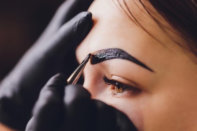 美容師-メイクアップアーティストは、セッション修正で以前に摘み取ったデザインのトリミングされた眉にペイントヘナを適用します。顔の専門的なケア。