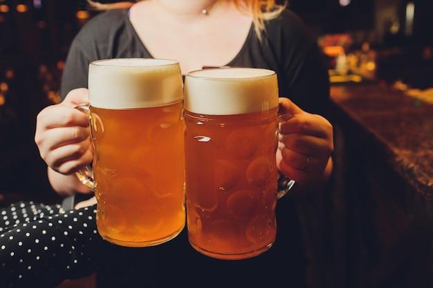 Официант сервирует бокалы с холодным пивом на подносе.