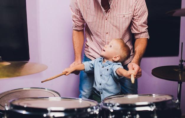 Маленький мальчик играет барабаны в студии звукозаписи.