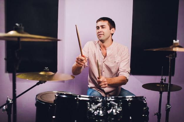 Молодой человек за барабанной установкой в профессиональной студии звукозаписи.