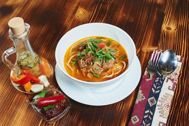 木製のテーブルにオリエンタルラグマンウズベキスタンのスープ。