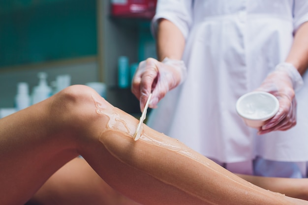Нанесение контактного геля перед процедурой лазерной эпиляции. применение сахарной пасты для процедуры шугаринга.