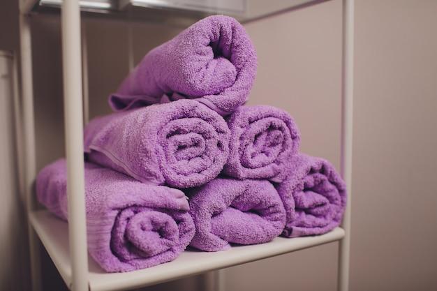 Стек витой махровые полотенца на полке.