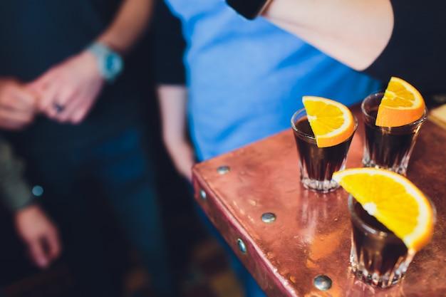 Три алкогольный напиток в рюмки с апельсиновые дольки в деревянный стол.