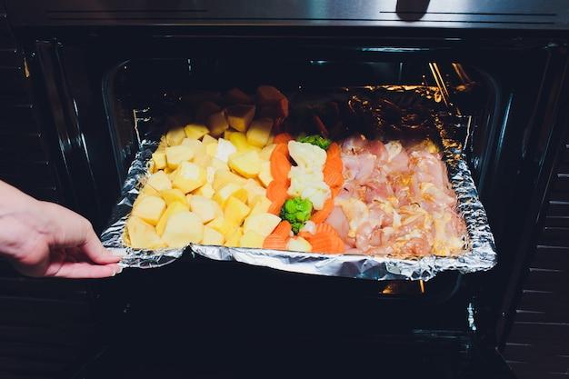 オーブンから野菜と一緒に揚げた焼き鳥を取って調理します。家庭料理のコンセプト。