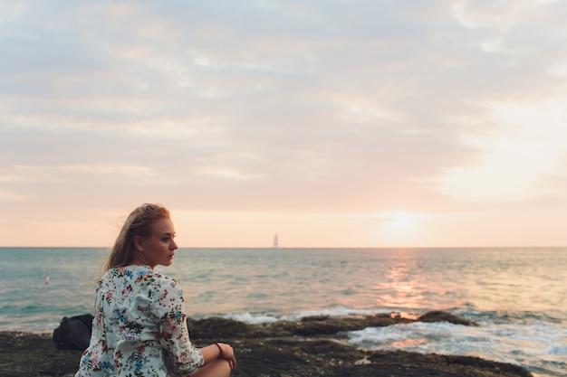 休暇を楽しんでいます。海ビューポイントで夕日を楽しむ若い旅行女性。