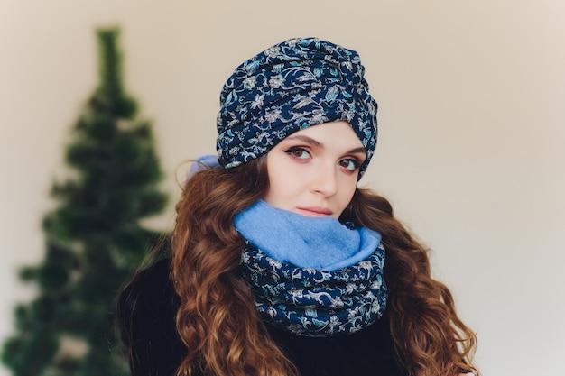 Удивлен счастливым красивая женщина, глядя в сторону в волнении. девушка рождества нося связанную теплую шляпу и варежки, изолированные на серой предпосылке.