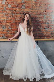 Красивая женщина позирует в свадебном платье.