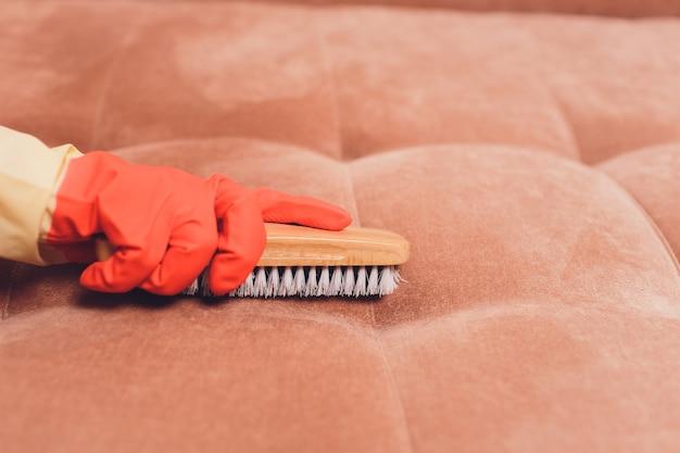 Женские руки с кисточкой для чистки дивана
