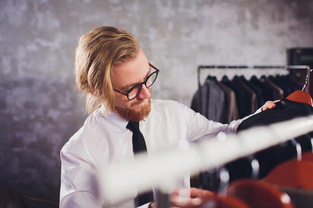 Мужской клиент ищет куртку в магазине мужской одежды.