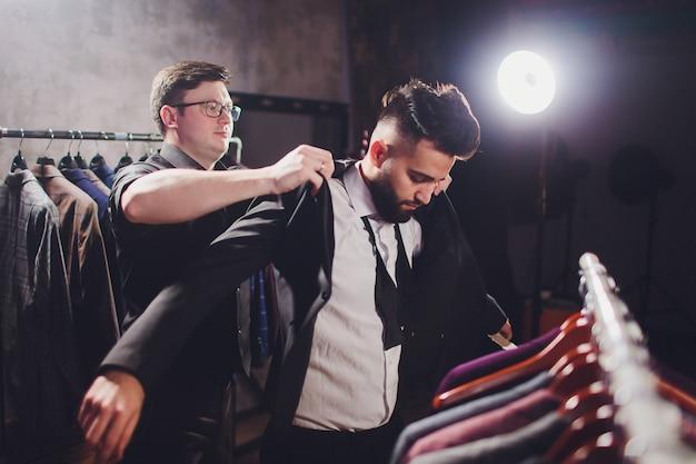 Мужской клиент в торговом центре пробует деловую одежду с помощью продавца