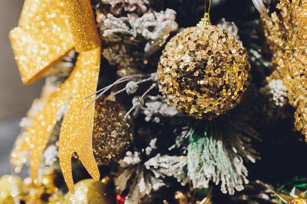 Золотой новогодний фон из де-сфокусированных огней с украшенным деревом.