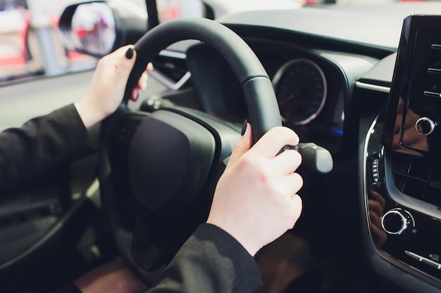 車を運転する女性は、ステアリングホイールのクローズアップに手します。