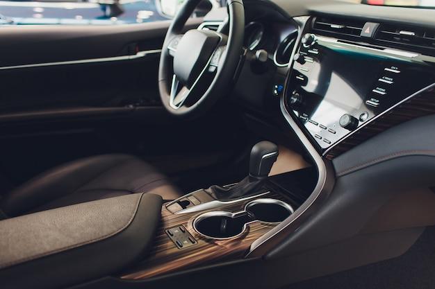 ブラックサロンが付いている車の内部ビュー。ステアリングホイール、自動