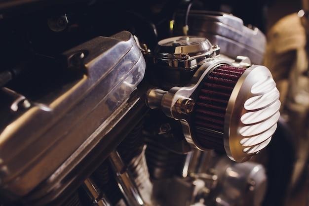 オートバイエンジン、排気管とメタリックな背景。
