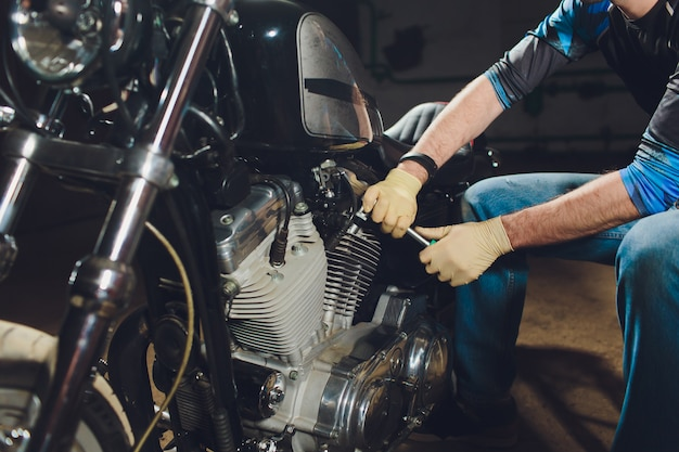 Человек, чинящий велосипед. уверен, молодой человек, ремонт мотоциклов возле своего гаража.