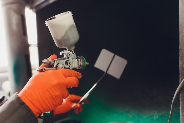 車の修理サービス。塗装前にカラーマッチングをチェックする労働者の画家。フィッティングプレートに黒い液体を噴霧します。