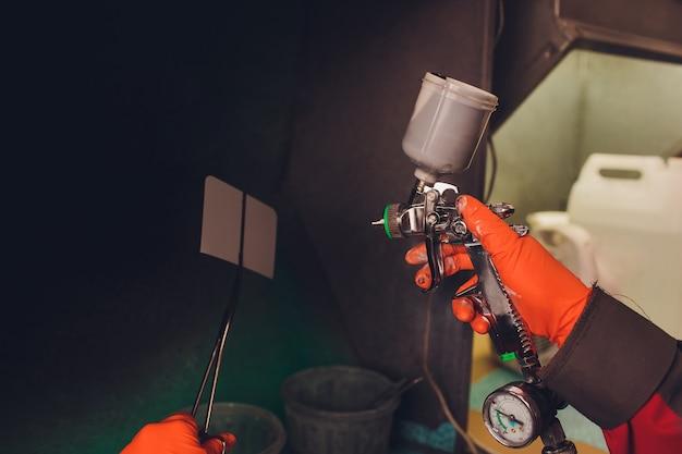 Автосервис. рабочий маляр проверяет соответствие цвета перед покраской. распыляя черную жидкость на установочную пластину.