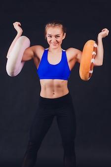 Молодая женщина фитнеса с руками в перчатках показывая плотные мышцы живота