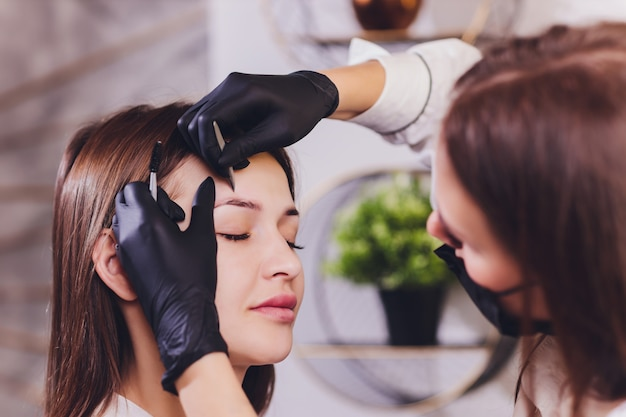 美容師-メイクアップアーティストは、セッション修正で以前に摘み取ったデザインのトリミングされた眉毛にペイントヘナを適用します。顔の専門的なケア。