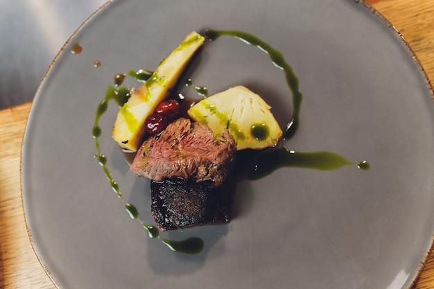 白いプレートの牛ヒレ肉のスペアリブ、根菜、チェリーアーモンド。