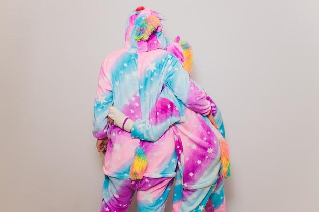 ユニコーンきぐるみの衣装を着て、コスプレやパジャマパーティーの準備をしている女の子。白い背景にポーズをしながらカメラを見てパジャマを着た若い女性。