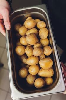 Сырая картошка в кожуре в металлическом шаре.