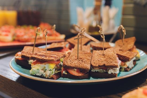 チキンビーコンハム、エッグサラダコールドカットブリオッシュサンドイッチ、ケータリング、セミナー、コーヒーブレーク、朝食、ランチ、ディナー、ビュッフェ、ミーティンググループ用のミニクラブサンドイッチ。
