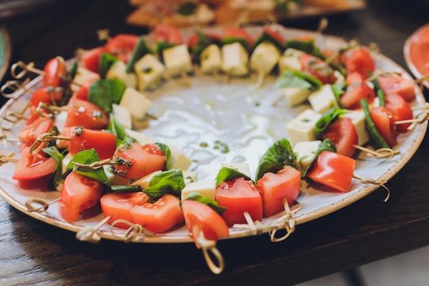 スナックカナッペ揚げパントマトパセリとサラミを提供するクローズアップの大皿。