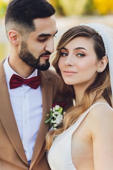 スタイリッシュな幸せな新郎新婦は屋外の結婚披露宴で夜の光の中で大きな愛の言葉でポーズします。夜の公園で楽しんでいる新婚夫婦の豪華な結婚式のカップル。