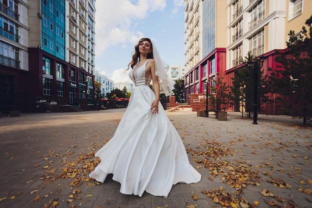Невеста позирует в зеленом парке девушка в белом платье на фоне зеленого.