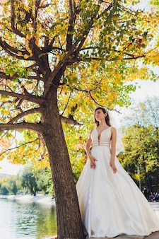 緑の背景に白いドレスの緑豊かな公園の女の子でポーズの花嫁。