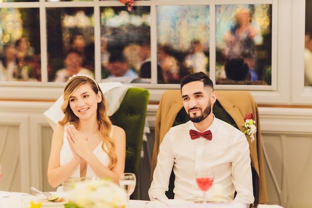 レストランで結婚披露宴で花で飾られた美しいピンクのセンターピースで一緒に座っているスタイリッシュな新郎新婦。モダンなケータリング。