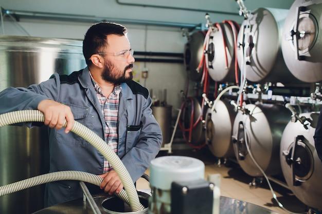 醸造所の職場でビールを作っている醸造家の肖像画..