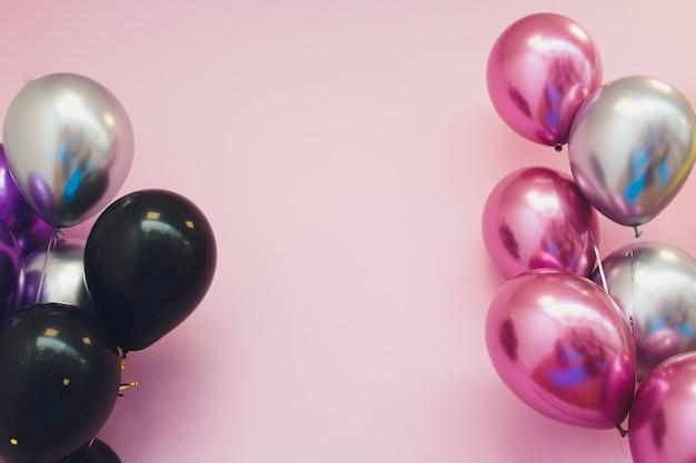 Концепция дня рождения - близкая вверх красочных воздушных шаров над предпосылкой кирпичной стены.
