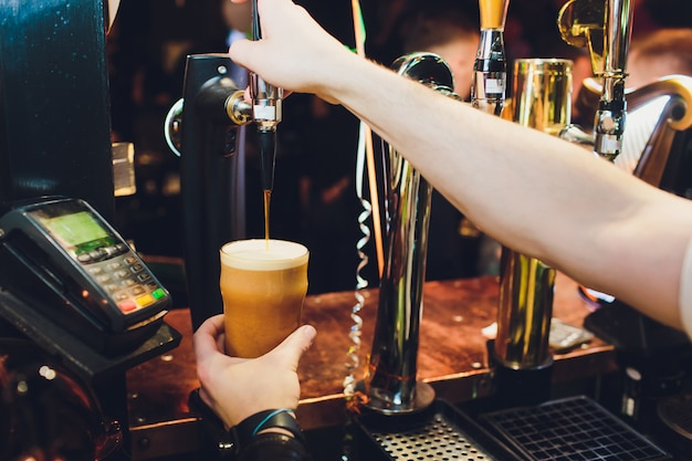 Бармен наливает из крана свежее пиво в стакан в пабе.